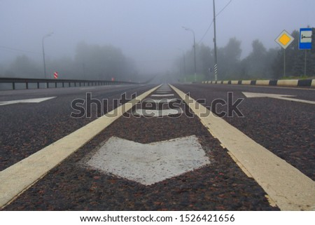 White road marking lines on an early morning foggy autumn on the freeway. Freeway empty, nobody on the road. Highway marking lines. #1526421656
