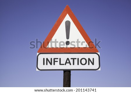 White road warning triangle with black  exclamation point and red frame on  a wooden mast in front of a blue sky. A second rectangular sign warns in english about inflation