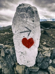 White rock, with an arrow and a heart. A sign pointing to love.