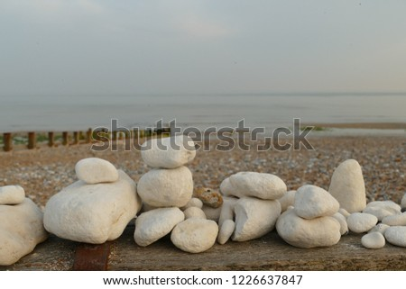 White rocks stacked into piles in the foreground, with a pebble beach, groyne and the sea in the background. Ferring beach, West Sussex, England, UK #1226637847