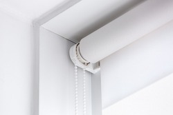 white rolled textile blinds on the window in a room corner, object of protection against sunlight close up.