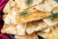 White Roman pizza with rosemary and coarse salt in closeup. Roman focaccia. Scrocchiarella.