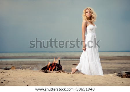 White romance. A barefoot woman wearing a white dress on the beach near an open fire.