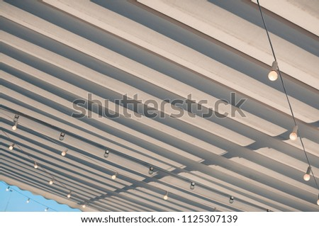 White roofing of a terrace in a street café or restaurant, with bulbs hanging under the awning, in the midday sun against blue sky #1125307139