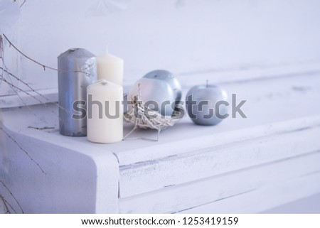 White room christmas interior decor with hand-made candle and bouq on a white piano
