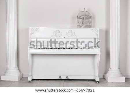 White room with columns and the piano about a wall