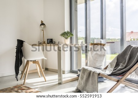 Photo of  White room with deckchair, wooden desk, chair and window wall