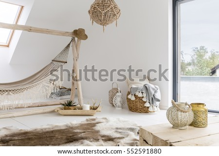 White room with hammock, window and wooden accessories