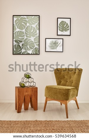 White room with monstera leaf wall decor and green armchair