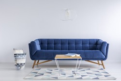 White room with pattern carpet, blue sofa and table
