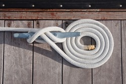 White rope coiled on a wooden dock and tied to a metal cleat.