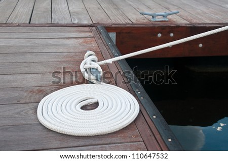 White rope coiled on a wooden dock and tied to a metal dock cleat.  Cleats are used for securing docks and lines from boats