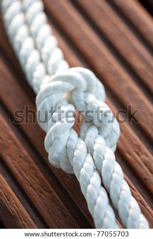 White rope with a knot on wooden background