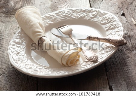 White rose patterned dinner plate with silverware and a napkin in an informal table setting