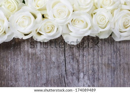 White roses on wooden background. Selective focus, copy space