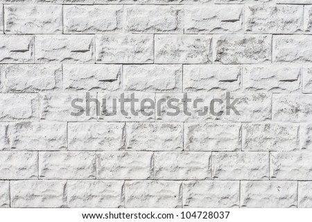white roughly textured brick wall painted with white paint