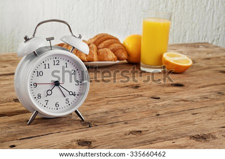 White round alarm clock on a wooden table in the kitchen with croissants and orange juice. Copy space. Free space for text or object #335660462