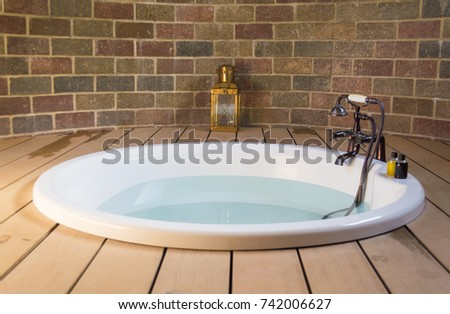 white round bathtub on wooden...