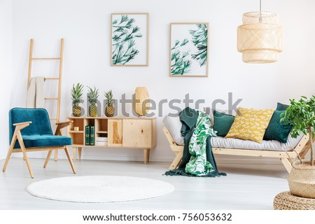 White round carpet in rustic living room with gold pillow on beige couch and pineapples on wooden cupboard Foto stock ©