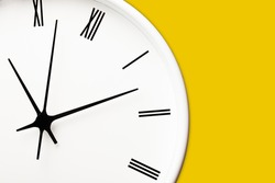 White round clock with black arrows and numbers on yellow wall. Time symbol background.Hours and minutes texture. Empty copy space isolated clock. Daily hourly routine backdrop.