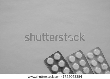 Photo of white round pills, three packs of pills, located on the bottom of the image on a gray background, with free space for text