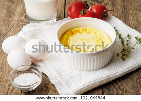 white round ramekin with oven-baked omelet of eggs and milk, with a ingredients - tomatoes, eggs, salt, glass of milk on brown rustic wooden table, side view.