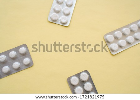 Photo of white round tablets, four packs of tablets, located on one package on each side of the image on a yellow background, with free space for text in the center