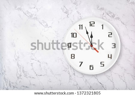 White round wall clock on white natural marble background. Almost twelve midday or midnight concept