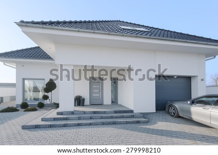 White royal residence with garage and new silver car