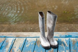 White, rubber, Shrimper boots, on a wooden porch, during Hurricane Laura, with rising floodwater in the background, located off the coast of South Louisiana.