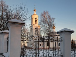 White Russian church with golden domes at dawn on a clear winter morning. The rising sun illuminates the top of the bell tower. View from outside the fence. No people