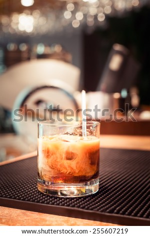 White russian cocktail on the bar stand on rubber mat. Shallow DOF and marsala tonned #255607219
