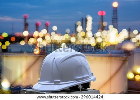 white safety helmet standing in front of oil refinery background