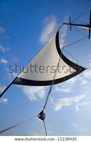White sail and pulley rigging against blue sky