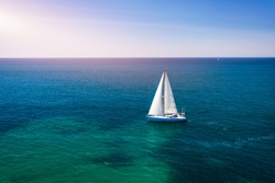 White sail boat isolated in blue sea water. Sailboat in the sea in the sunlight, luxury summer adventure, active vacation in Mediterranean sea. Yacht sailing on opened sea. Sailing boat.