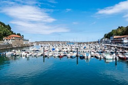 White sail boats in Mutriku port and old town, Basque country, Spain. View of colorful boats docked on Motrico marina facing the Cantabric sea.