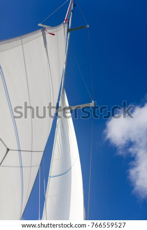 White sailboat sail blown up by wind against a clear blue sky in New Zealand #766559527