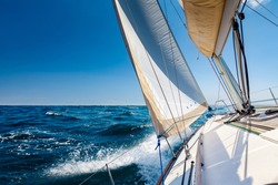 White sailing boat at open sea in sunshine