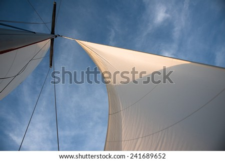 White sails and mast against blue sky with some clouds on the windful day