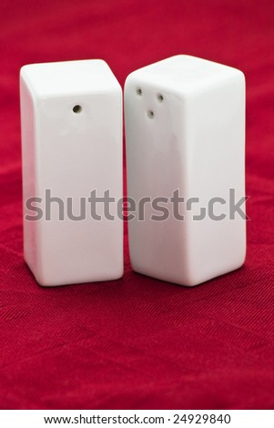white salt and pepper shakers isolated on dark red table cloth