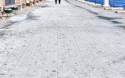 White salt stains on pedestrian paving slabs. Salty surface, salt on paving slabs outdoors. Rock salt (sodium chloride) used on paving slabs and asphalt roads for deicing. Salt is de-icing agent