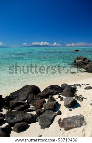 White sand beach with volcanic rock on beautiful Bora Bora island in French Polynesia