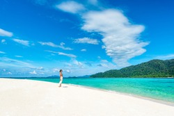 White Sand Beaches with Woman looking at the Clear water turquoise color on the Sunrise Beach on the Lipe island, Satun, Thailand.
