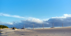 White sand dune against blue sky with Stratus and Cirrus clouds. Panoramic natural landscape. Big dune of Valdevaqueros inlet in Tarifa coast, Cadiz, Andalusia, Spain