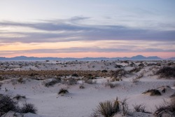 White sand dunes with a pastel sunset background
