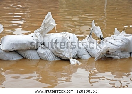 White sandbags for flood defense and brown water
