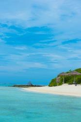 White sandy beach of Maldives, blue sky, vertical