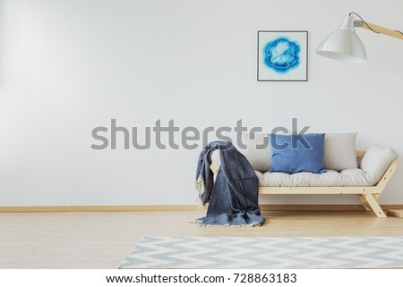 White scandinavian room with wooden sofa and blue accents, jean pillow, blanket and pastel zigzag rug #728863183