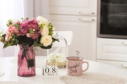 White scandinavian style kitchen interior. Vase with flowers, a pink mug and the number 8 on the table. Happy Women's Day holiday concept.