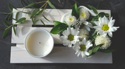 white scented candle and delicate flowers on wooden rack. home fragrances for relaxation and calm. flower fragrance for home. unbranded ceramic candle. top view
